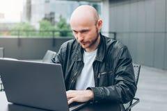 Atrakcyjny dorosły pomyślny łysy brodaty mężczyzna w czarnej kurtce z laptopem w ulicznej kawiarni przy miastem obrazy royalty free