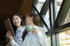 Atrakcyjny dwa azjata bizneswoman pije kawę i używa cyfrową pastylkę obrazy royalty free