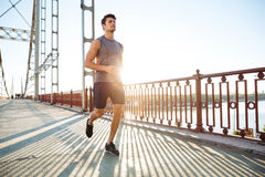 Atrakcyjny dysponowany mężczyzna bieg wzdłuż mosta przy zmierzchu światłem Obraz Royalty Free