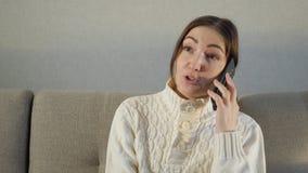 Atrakcyjny dziewczyny obsiadanie na kanapie w domu i opowiadający na jej telefonie zdjęcie wideo
