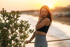 Atrakcyjny dziewczyny odprowadzenie na molu blisko morza w zmierzchu czasie zdjęcie royalty free
