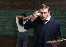 Atrakcyjny elegancki nauczyciela dylemat jego szkła na twarzy z palcem, mieć książkę w ręce w klasie fotografia royalty free