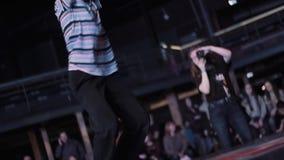 Atrakcyjny energiczny nastoletni chłopak w koszulce z lampasami breakdancing na scenie zdjęcie wideo