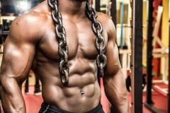 Atrakcyjny hunky czarny męski bodybuilder pozuje z żelaznymi łańcuchami Obrazy Stock