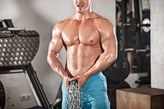 Atrakcyjny hunky czarny męski bodybuilder robi bodybuilding pozie w gym z żelaznymi łańcuchami zdjęcia royalty free
