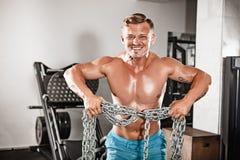 Atrakcyjny hunky czarny męski bodybuilder robi bodybuilding pozie w gym z żelaznymi łańcuchami obraz royalty free