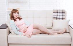 Atrakcyjny i piękny w średnim wieku kobiety obsiadanie na kanapie i relaksować w domu przekwitanie obraz stock