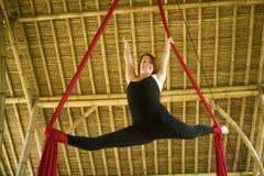 Atrakcyjny i sportowy aerialist kobiety obwieszenie od jedwabniczej tkaniny robi powietrzny dancingowy treningu trenowa? szcz??li fotografia stock
