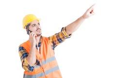 Atrakcyjny inżynier wskazuje palec upwards podczas gdy używać cellphon Obraz Royalty Free