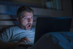 Atrakcyjny interneta nałogowa mężczyzna w szoka i niespodzianki networking nocnym na łóżku zaskakiwał twarzy wyrażeniowego działa obrazy royalty free