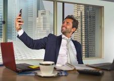 Atrakcyjny inwestor lub duży firmy CEO pracuje przy biurowym biurkiem pokazuje daleko brać selfie fotografię z telefonem komórkow obrazy stock