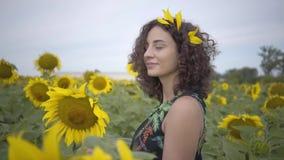 Atrakcyjny kędzierzawy kobiety odprowadzenie na słonecznikowym polu Jaskrawy ? zdjęcie wideo