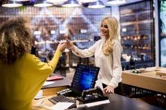 Atrakcyjny kobieta klient płaci z kartą kredytową w mody sho obrazy royalty free