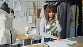 Atrakcyjny kobieta krawczyna rozkazuje tkaninę dla jej nowej odzieżowej kolekci na telefonie komórkowym i patrzeje nakreślenia zbiory