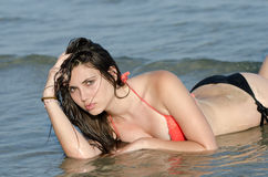 Atrakcyjny kobiety kłamstwo w morzu jest ubranym swimwear Zdjęcie Stock