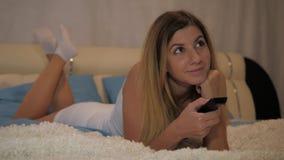 Atrakcyjny kobiety lying on the beach Na łóżku Używa TV pilota Podrzuca Przez kanałów zbiory
