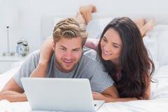 Atrakcyjny kobiety obejmowania mąż podczas gdy używać laptop obraz royalty free