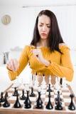 Atrakcyjny kobiety obsiadanie przed szachy - czuć szykany zdjęcia royalty free
