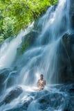 Atrakcyjny kobiety obsiadanie przy skałą w joga pozie dla duchowego relaksu spokoju, medytaci przy oszałamiająco piękną siklawą i fotografia stock