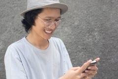 Atrakcyjny młody azjatykci mężczyzna z kapeluszem i szkłami używać smarphone i ono uśmiecha się obraz stock