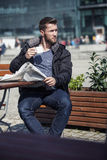 Atrakcyjny mężczyzna czyta wiadomość papier siedzi w sklep z kawą fotografia stock