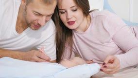 Atrakcyjny mężczyzna i kobieta patrzeje słodkiego sypialnego dziecka w sypialni zbiory