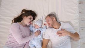 Atrakcyjny mężczyzna i kobieta patrzeje słodkiego sypialnego dziecka w sypialni zbiory wideo