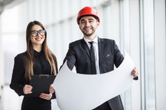 Atrakcyjny mężczyzna i kobiety biznes zespala się pracującą budowę na placu budowy blisko panoramicznych okno Zdjęcie Stock
