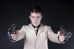 Atrakcyjny mężczyzna jest ubranym białego kostium z pistoletem Zdjęcia Royalty Free