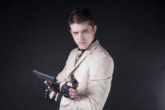 Atrakcyjny mężczyzna jest ubranym białego kostium z pistoletem Fotografia Stock