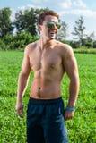 Atrakcyjny mężczyzna jest ubranym okulary przeciwsłonecznych siedzi w parku fotografia stock
