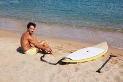 Atrakcyjny mężczyzna obsiadanie na gorącym piasku blisko oceanu Zdjęcie Stock