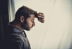 Atrakcyjny mężczyzna opiera na nadokiennego cierpienia emocjonalnym kryzysie i depresji Fotografia Stock