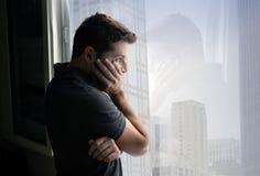 Atrakcyjny mężczyzna patrzeje przez nadokiennego cierpienia emocjonalnego kryzysu i depresji