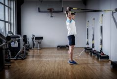 Atrakcyjny mężczyzna podczas treningu z zawieszenie patkami W Gym zdjęcie stock