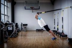 Atrakcyjny mężczyzna podczas treningu z zawieszenie patkami W Gym obraz stock