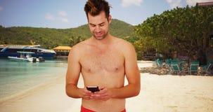 Atrakcyjny mężczyzna przy kurortem używać datujący app na jego telefonie obrazy stock