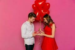 Atrakcyjny mężczyzna robi teraźniejszości dla jej ładnej dziewczyny na St walentynki ` s dniu Obrazy Stock