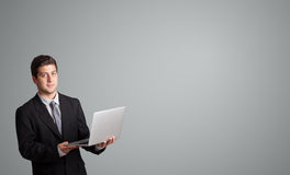 Atrakcyjny mężczyzna trzyma laptop i przedstawia kopii przestrzeń Obrazy Stock