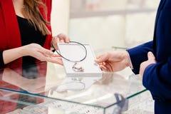 Atrakcyjny mężczyzna wybiera kolia prezent w sklepie jubilerskim z brodą Fotografia Stock