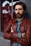 Atrakcyjny mężczyzna z gęstą brodą, stoi przed wejściem przy hotelem Obrazy Stock