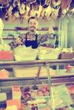 Atrakcyjny męski sklepowy asystent demonstruje rodzaje mięso w sh Zdjęcia Royalty Free