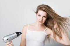 Atrakcyjny młoda dziewczyna cios suszy jej włosy i patrzeje kamerę Fotografia Stock