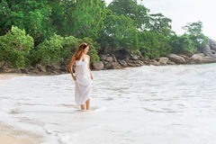Atrakcyjny, młoda kobieta odprowadzenie na wybrzeżu, i ciągnięcie w górę sukni zdjęcia stock