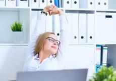 Atrakcyjny, młoda kobieto w szkłach, rozciąga przy jej miejscem pracy i ono uśmiecha się w biurze obrazy stock