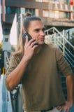 Atrakcyjny młodego człowieka modniś opowiada na smartphone podczas gdy siedzący na krokach szklany centrum biznesu Miastowy szybk obraz royalty free