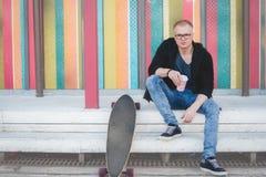 Atrakcyjny młodego człowieka obsiadanie na drewnianych krokach w miastowego miasta parkowej pije kawie z jego łyżwiarstwo deską, zdjęcia stock
