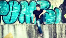 Atrakcyjny młodego człowieka obsiadanie przeciw graffiti ścianie zdjęcia stock