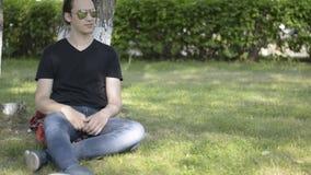 Atrakcyjny młodego człowieka obsiadanie w parku drzewem i stawia dalej okulary przeciwsłonecznych zbiory