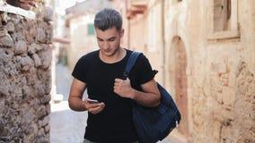 Atrakcyjny młodego człowieka odprowadzenie wokoło starego miasta z z plecakiem Mężczyzna wybiera numer liczbę na telefonie komórk zbiory wideo